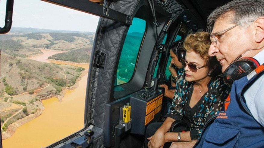 In this photo released by the official web site of the Brazilian Presidency, President Dilma Rousseff accompanied by Minas Gerais state Gov. Fernando Pimentel, looks out over the area of dam bursts at an iron ore mine, in the southeastern Brazilian state of Minas Gerais, Thursday, Nov. 12, 2015. Last week dam failures unleashed a deadly wave of viscous mud that all but erased a hamlet and contaminated a key river. Rousseff says the mining company, Samarco, will be made to pay for the cleanup. (Roberto Stuckert Filho/Brazil Presidential Press Office via AP)