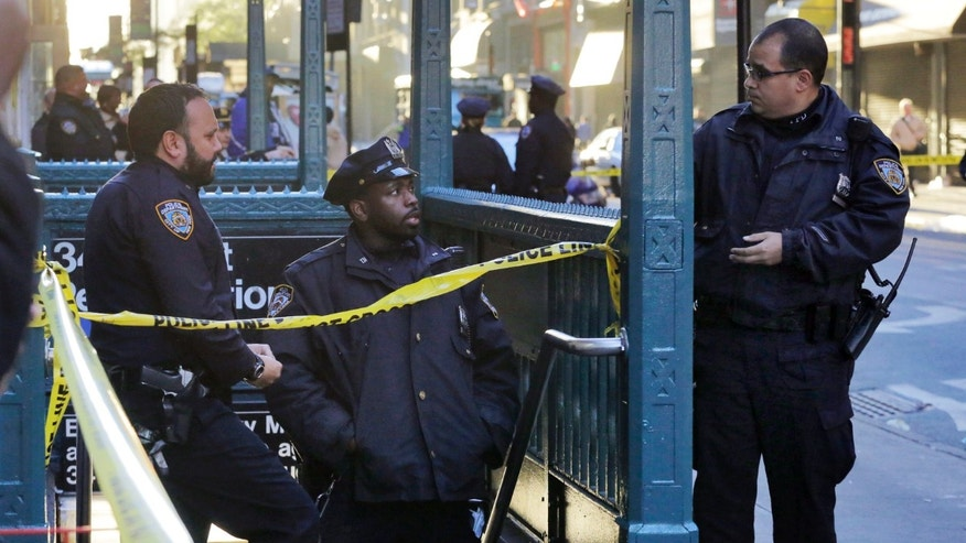 New York Police Department officers investigate a shooting at a subway station entrance at 35th Street and Eighth Avenue, Monday, Nov. 9, 2015, in New York. Authorities said three people have been shot, one fatally. No suspects were immediately arrested. (AP Photo/Mark Lennihan)