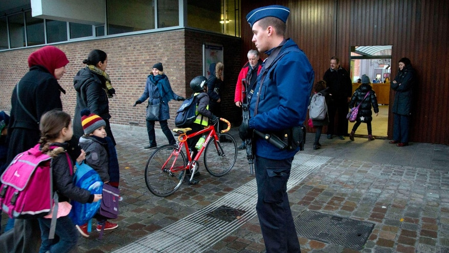 Nov. 25, 2015: Children pass a police officer as they arrive for school in the center of Brussels.