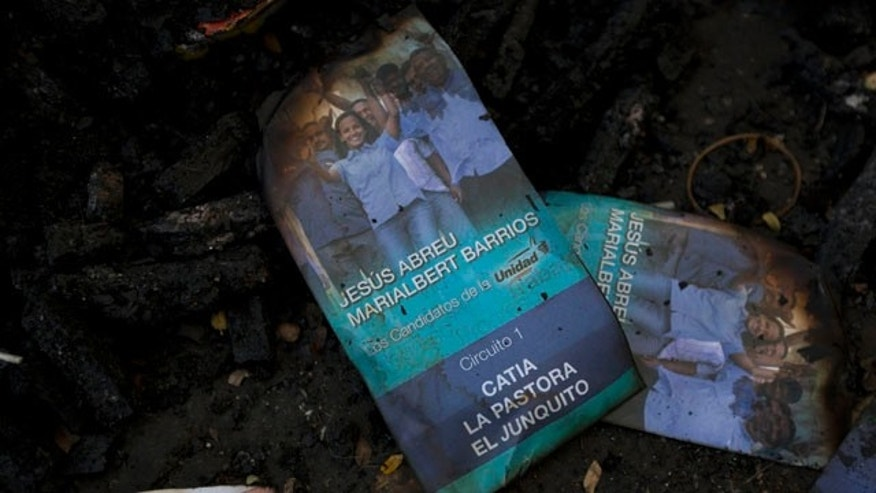 Nov. 24, 2015: Singed flyers promoting opposition congressional candidate Marialbert Barrios is seen on top of a trash pile at the Catia neighborhood, in Caracas, Venezuela. Remains of burned flyers and posters of opposition congressional candidates show traces of a battle that was fought in a busy street in the populous neighborhood Tuesday, after a group of alleged government supporters, some armed and on motorbikes, arrived and violently attacked supporters of the opposition as they hung election posters and flyers promoting their candidates. (AP Photo/Ariana Cubillos)