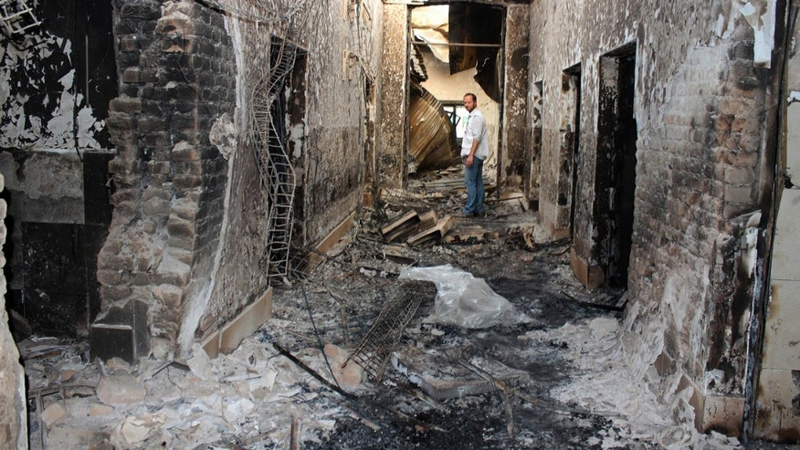 FILE - In this Oct. 16, 2015, file photo, an employee of Doctors Without Borders stands inside the charred remains of their hospital after it was hit by a U.S. airstrike in Kunduz, Afghanistan.