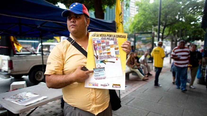 An activist of the opposition Primero Justicia or Justice First political party, holds a poster showing how to vote in the next congressional elections, in Caracas, Venezuela, Thursday, Nov. 26, 2015. An opposition leader was shot to death Wednesday while campaigning for next week's congressional elections in Venezuela, members of his political party said. The shooting took place in the central town of Altagracia de Orituco, said the leader of the Democratic Action Party, Carolos Prosperi. He said he heard gunshots as the rally was breaking up and the town's party leader Luis Manuel Díaz, was hit. (AP Photo/Ariana Cubillos)