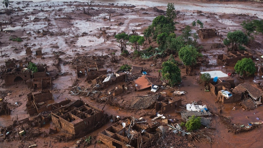 In this Nov. 6, 2015 photo, homes lay in ruins after two dams burst the previous day, flooding the small town of Bento Rodrigues in Minas Gerais state, Brazil. Searchers used small airplanes and a drone to look for missing people after dams broke inside an iron ore mine. The mine operator Samarco is jointly owned by the Brazilian mining company Vale and Australia's BHP Billiton. (AP Photo/Felipe Dana)