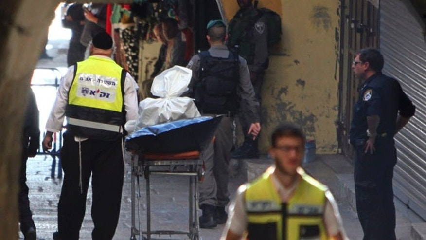 An emergency service member stands next to the body of a Palestinian in Jerusalem's Old City.