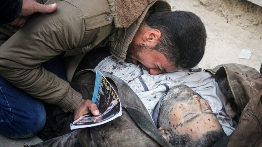 In this photo provided by the Syrian anti-government activist group Ariha Today, a Syrian man weeps on the body of a victim who was killed by airstrikes believed to be carried out by Russian warplanes.