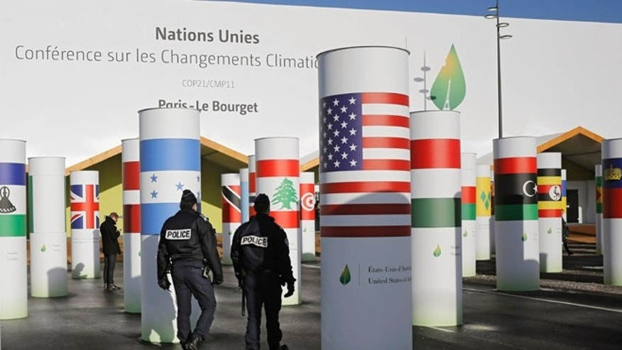 FILE - Policemen patrol outside the main entrance of the United Nations Climate Change Conference in Le Bourget, outside Paris, Saturday, Nov. 28, 2015. The site of Paris-Le Bourget will officially become United Nations territory for the COP 21 conference which is scheduled to start on Nov. 30.   President Barack Obama heads to a historic conference in Paris hoping to marshal strong global action against climate change.  (AP Photo/Laurent Cipriani, File)