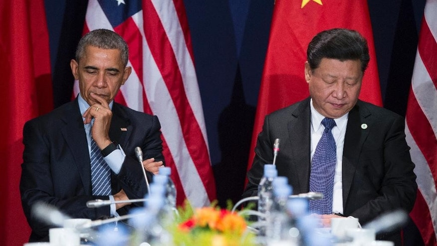 U.S. President Barack Obama, left, and Chinese President Xi Jinping look down during their meeting held on the sidelines of the COP21, United Nations Climate Change Conference, in Le Bourget, outside Paris, on Monday, Nov. 30, 2015. (AP Photo/Evan Vucci)
