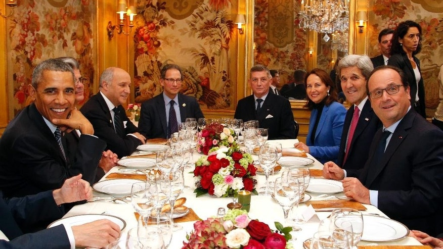 President Barack Obama, left, sits with French President Francois Hollande, right, as they have dinner at the Ambroisie restaurant in Paris, France, with Secretary of State John Kerry, 2nd right, French Minister for Ecology, Sustainable Development and Energy Segolene Royal, 3rd right, and French Foreign Minister, Laurent Fabius, 3rd left, Monday, Nov. 30, 2015. Obama is in France for a two-day visit as part of the COP21, the United Nations Climate Change conference. Other officials are : Translator, Thomas Ronkin, 2nd left, Charles Kupchan, top left, and French President Hollande's Military Chief of Staff General Benoit Puga, top right. (AP Photo/Thibault Camus, Pool)