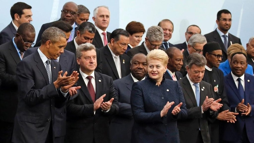 CORRECTS ID TO LITHUNIA PRESIDENT  U.S. President Barack Obama, left, and Lithuania's President Dalia Grybauskaite, front row third from right, applaud as they pose with world leaders for a group photo at the COP21, United Nations Climate Change Conference, in Le Bourget, outside Paris, Monday, Nov. 30, 2015. (AP Photo/Jacky Naegelen, Pool)