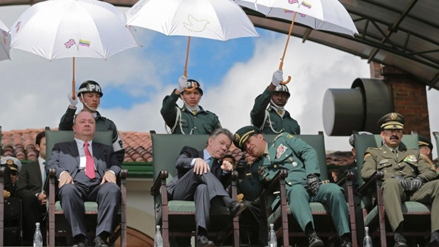 In this Thursday, July 9, 2015, file photo, Colombia's President Juan Manuel Santos, center left, leans in to listen to Colombia's Armed Forces Commander Gen. Juan Pablo Rodriguez, during a military ceremony in Bogota, Colombia. While all Colombian men must register for the draft at age 18, itâs mostly poorer men who are compelled to serve in this nation of 46 million people. They canât afford the escape route: Enrolling in college and paying a special sliding-scale tax of between $300 and $1,200. As a result, 90 percent of drafted youths come from the lower classes, the Colombian Collective of Conscientious Objectors says. (AP Photo/Fernando Vergara, File)