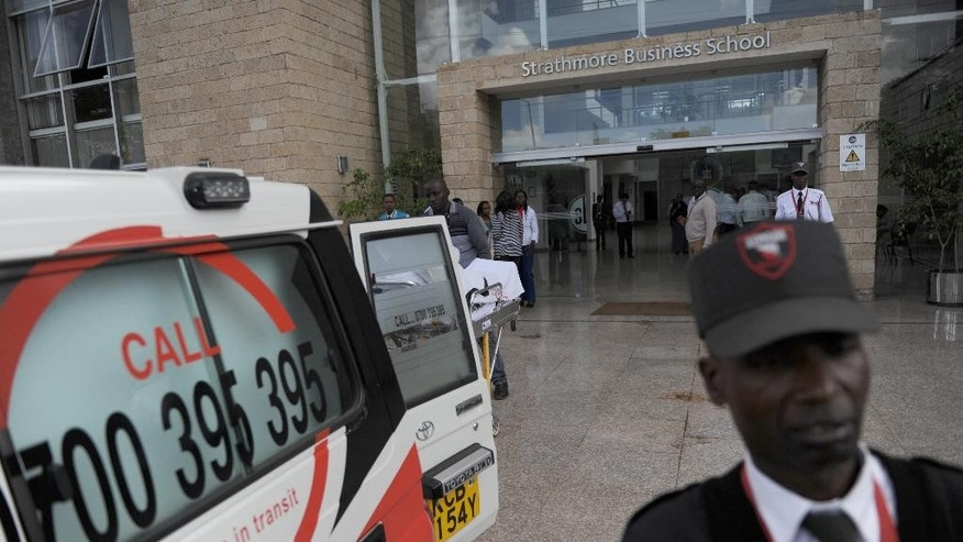 In this photo of Monday, Nov. 30, 2015, an ambulance and a security guard outside the University  after gunshots were heard at Strathmore University in Nairobi, Kenya,  Monday morning.  A drill to test terrorism preparedness at a leading Kenyan university led to a stampede in which one person died and 20 others were injured, the institution said Monday. Strathmore University said in a statement that one staff member had died as a result of injuries received during the drill aimed at testing the preparedness of the university community and emergency response team in the event of an attack.(AP Photo/John Muchucha)