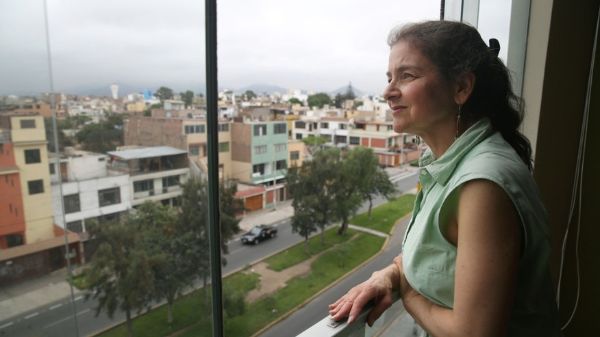 In this Friday, Nov 27, 2015 photo, U.S. activist Lori Berenson looks out from her residence in Lima, Peru. Berenson is heading home to New York,  two decades after being found guilty of aiding leftist rebels. The 46-year-old has been living quietly in Lima with her 6-year-old son since her 2010 parole. Sheâs been barred from leaving the country until her 20-year sentence lapsed. (AP Photo/Martin Mejia)