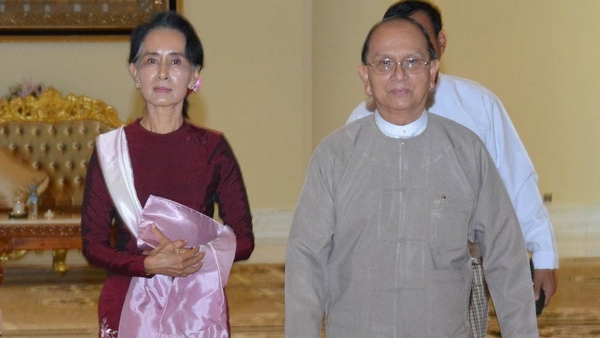 In this image provided by the Myanmar Ministry of Information,  Myanmar President Thein Sein, right, walks with opposition leader Aung San Suu Kyi, at the presidential residence Wednesday, Dec 2, 2015, in Naypyitaw, Myanmar. Suu Kyi met Myanmar's outgoing president on Wednesday to discuss the transfer of power following her party's landslide election win. (Myanmar Ministry of Information via AP)