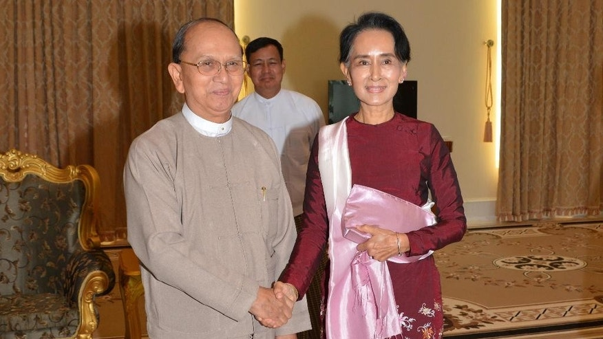 In this image provided by the Myanmar Ministry of Information, Myanmar President Thein Sein, left, shakes hands with opposition leader Aung San Suu Kyi during their meeting at the presidential residence Wednesday, Dec 2, 2015, in Naypyitaw, Myanmar. Suu Kyi met Myanmar's outgoing president on Wednesday to discuss the transfer of power following her party's landslide election win. (Myanmar Ministry of Information via AP)