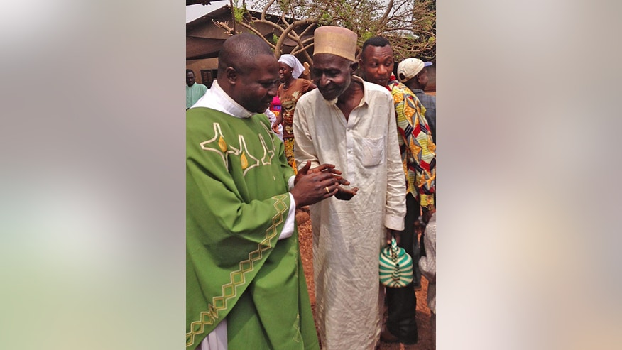 FILE - In this file photo taken on Sunday, Feb. 23, 2014, Father Justin Nary, left, greets Ousmane Mahamat, one of the 800 Muslims seeking refuge in a Catholic church in Carnot a town 200 kilometers (125 miles) from the Cameroonian border in Central African Republic. Father Justin Nary opened his gate to nearly 800 Muslims threatened with death from the roving gangs of Christian militia fighters who even threatened to burn his church down. Nearly a year later, 2015, more than 500 of the displaced are still living there in fear of going home. (AP Photo/Krista Larson,File)