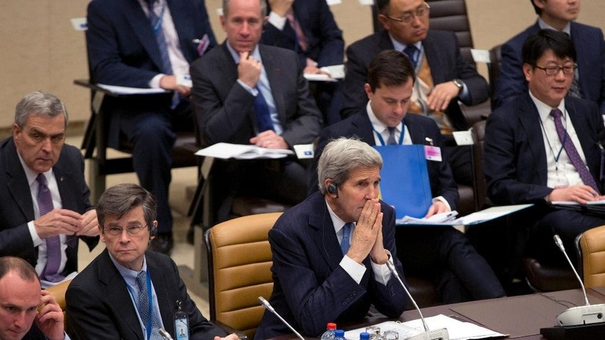 U.S. Secretary of State John Kerry, center, waits for the start of a round table meeting of Resolute Support at NATO headquarters in Brussels on Tuesday, Dec. 1, 2015. U.S. Secretary of State John Kerry and other NATO foreign ministers meet Tuesday to discuss Russia, beefing up the alliance's southern defenses and whether to expand NATO by adding Montenegro to the NATO Alliance. (AP Photo/Virginia Mayo)