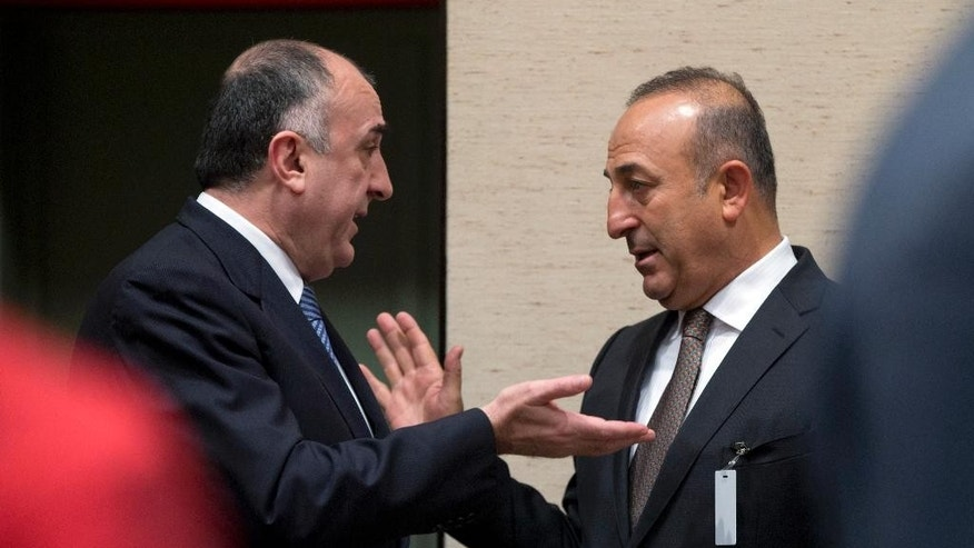 Turkish Foreign Minister Mevlut Cavusoglu, right, speaks with Azerbaijan's Foreign Minister Elmar Mammadyarov during a round table meeting of Resolute Support at NATO headquarters in Brussels on Tuesday, Dec. 1, 2015. U.S. Secretary of State John Kerry and other NATO foreign ministers meet Tuesday to discuss Russia, beefing up the alliance's southern defenses and whether to expand NATO by adding Montenegro to the NATO Alliance. (AP Photo/Virginia Mayo)