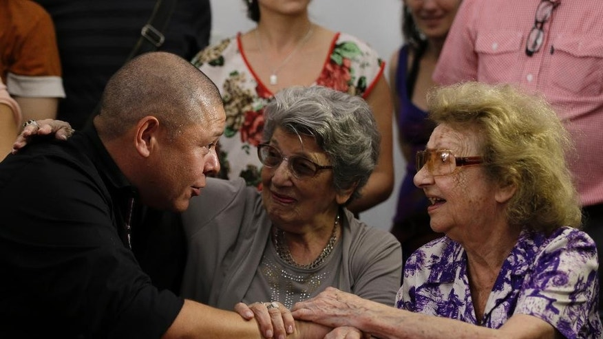 Mario Bravo, left, holds hands with members of the Humans Rights organization Abuelas de Plaza de Mayo during a press conference to announce that he was identified as a child who was taken from his mother as an infant while she was in jail during the military government and given to foster fathers in Buenos Aires, Argentina, Tuesday, Dec. 1, 2015. Bravo is the 119th child to be found by the human rights group that has worked for decades to reunite families with missing children, stolen during Argentina's military dictatorship.(AP Photo/Ricardo Mazalan)