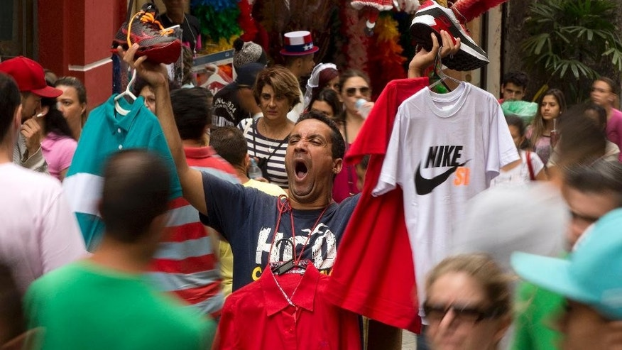 A street vendor sells shoes and shirts in Sao Paulo's shopping district, Brazil, Tuesday, Dec. 1, 2015. Latin America's largest economy has shrunk even more than expected, increasing fears about the well-being of a nation hammered by falling commodity prices and a massive corruption scandal. (AP Photo/Andre Penner)