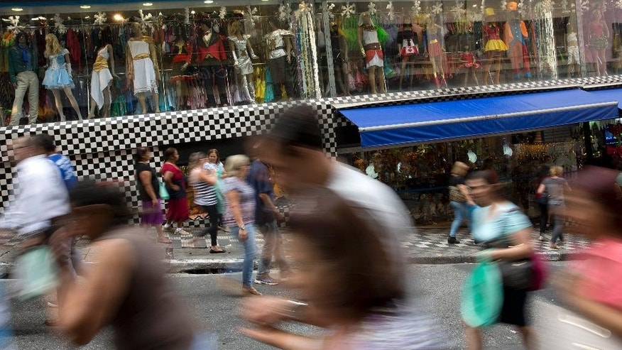 In this photo taken with a slow shutter speed, people walk through a shopping district in Sao Paulo, Brazil, Tuesday, Dec. 1, 2015. Latin America's largest economy has shrunk even more than expected, increasing fears about the well-being of a nation hammered by falling commodity prices and a massive corruption scandal. (AP Photo/Andre Penner)