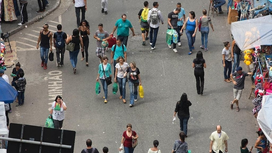 People walk through a shopping district in Sao Paulo, Brazil, Tuesday, Dec. 1, 2015. Latin America's largest economy has shrunk even more than expected, increasing fears about the well-being of a nation hammered by falling commodity prices and a massive corruption scandal. (AP Photo/Andre Penner)