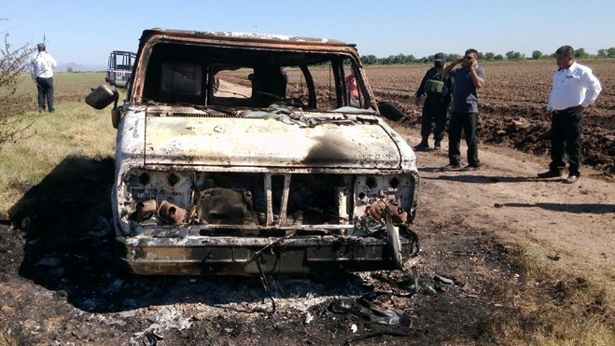 Nov. 21, 2015: Mexican authorities inspect a burnt out van suspected to belong to a couple of Australian tourists missing for more than a week, in Sinaloa, Mexico.