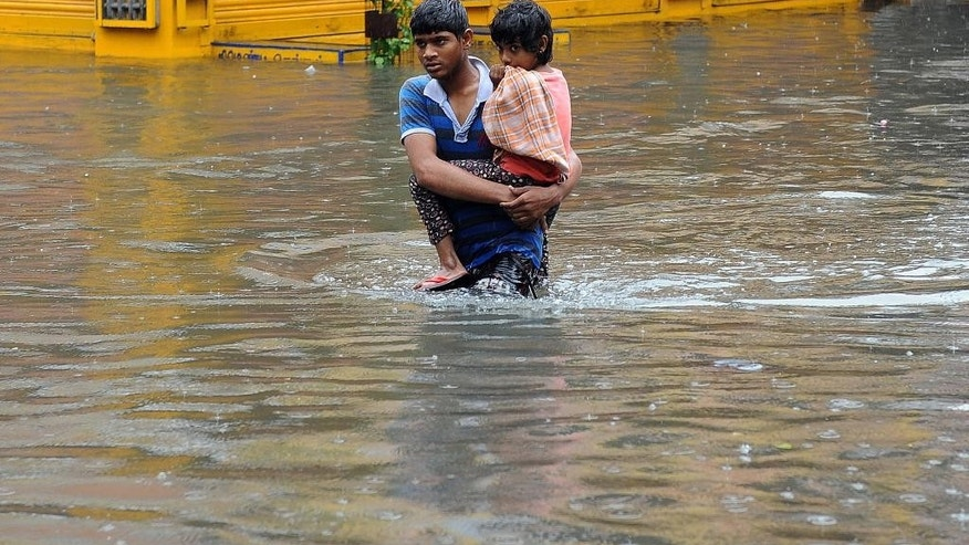 A boy carries a child and wades through a flooded street in Chennai, in the southern Indian state of Tamil Nadu, Wednesday, Dec. 2, 2015. Weeks of torrential rains have forced the airport in the state capital Chennai to close and have cut off several roads and highways, leaving tens of thousands of people stranded in their homes, government officials said Wednesday. (AP Photo)