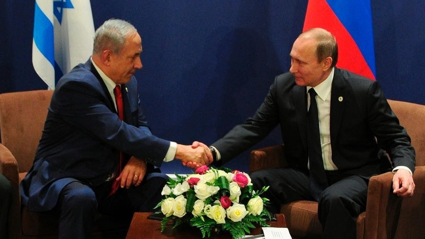 Russian President Vladimir Putin, right, and Israel's Prime Minister Benjamin Netanyahu shake hands during their meeting on the sidelines of the COP21 UN Conference on Climate Change in Paris, France, Monday, Nov. 30, 2015. (Mikhail Klimentyev/Sputnik, Kremlin Pool Photo via AP)