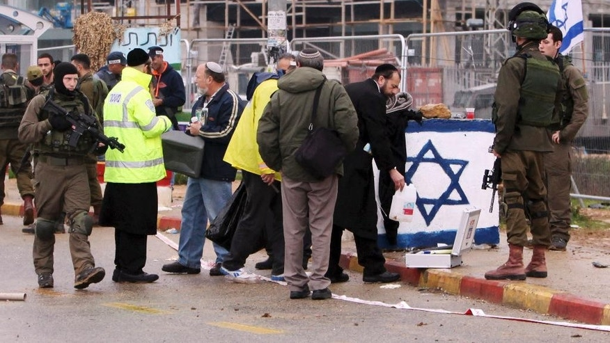 Israeli security stand at the scene of an alleged stabbing attack at Gush Etzion junction in the West Bank on Tuesday, Dec. 1, 2015. A Palestinian attempted to stab a pedestrian at a busy junction outside of Jerusalem when Israeli troops shot and killed him, the military said. (AP Photo/Mahmoud Illean)