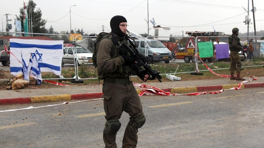 Israeli soldiers stand at the scene of an alleged stabbing attack at Gush Etzion junction in the West Bank on Tuesday, Dec. 1, 2015. A Palestinian attempted to stab a pedestrian at a busy junction outside of Jerusalem when Israeli troops shot and killed him, military said. (AP Photo/Mahmoud Illean)