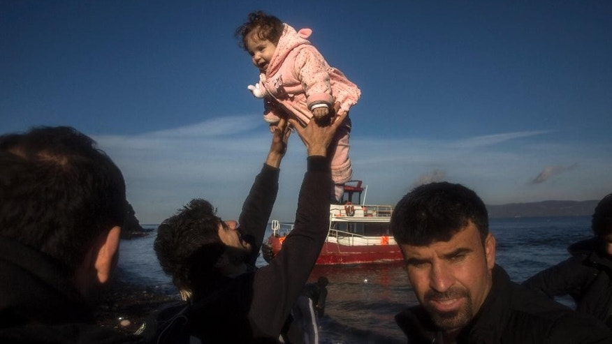 An Iraqi refugee from Mosul holds up his daughter after their arrival on a small vessel with about 150 other refugees and migrants, from the Turkish coast to the northeastern Greek island of Lesbos, on Tuesday, Dec. 1, 2015. Authorities in northwestern Turkey on Monday rounded up some 1,300 asylum seekers and migrants allegedly preparing to make their way into Greece. (AP Photo/Santi Palacios)