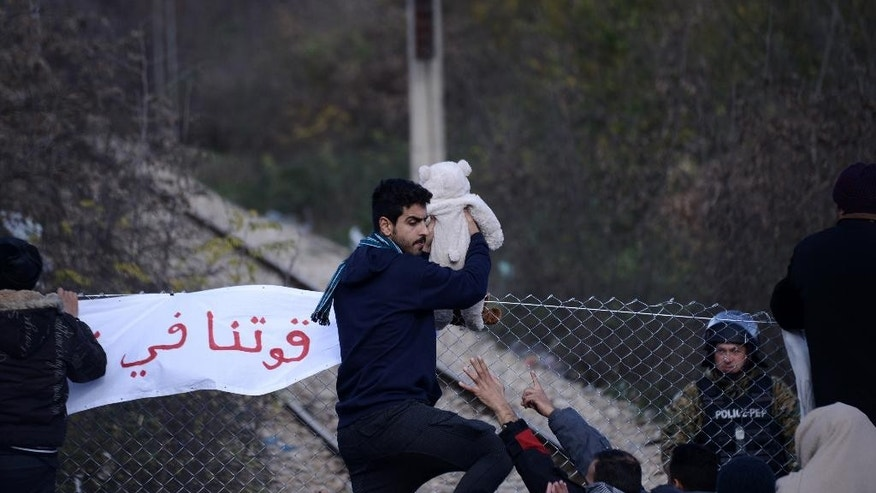 A man holds up a baby as stranded migrants protest in front of the border fence, demanding to cross the Greek-Macedonian border near the northern Greek village of Idomeni, Tuesday, Dec. 1, 2015. Hundreds of migrants are stranded on the Greek side after Macedonia blocked access to citizens of countries that are not being fast-tracked for asylum in the European Union. (AP Photo/Giannis Papanikos)