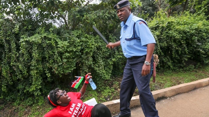 "A police officer hits a female demonstrator with his baton during an anti-corruption demonstration in downtown Nairobi, Kenya Tuesday, Dec. 1, 2015. Over a hundred demonstrators marched to the Supreme Court, Parliament, and State House on Tuesday to protest against corruption and demanding the government crack down on it, some carrying boxing symbols to represent the theme ""Knock out corruption"". (AP Photo/Brian Inganga)"