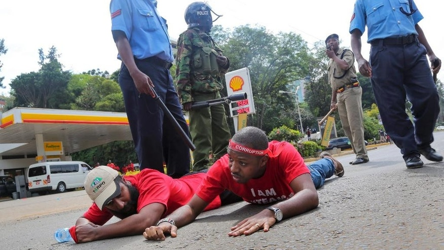 "Police and security forces arrest protest leader Boniface Mwangi, center, and another demonstrator during an anti-corruption demonstration in downtown Nairobi, Kenya Tuesday, Dec. 1, 2015.  Over a hundred demonstrators marched to the Supreme Court, Parliament, and State House on Tuesday to protest against corruption and demanding the government crack down on it, some carrying boxing symbols to represent the theme ""Knock out corruption"". (AP Photo/Brian Inganga)"