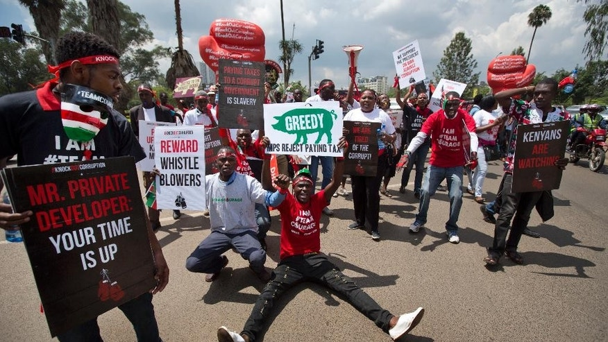 "Protesters sit down in the street during an anti-corruption demonstration in downtown Nairobi, Kenya Tuesday, Dec. 1, 2015. Over a hundred demonstrators marched to the Supreme Court, Parliament, and State House on Tuesday to protest against corruption and demanding the government crack down on it, some carrying boxing symbols to represent the theme ""Knock out corruption"". (AP Photo/Ben Curtis)"