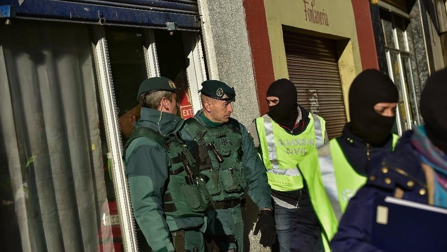 Spanish Civil Guard, leave the tea center where they detained an unidentified man of Morocco, in Pamplona, northern Spain, Tuesday, Dec. 1, 2015.  Spanish authorities allege the man is a suspected member of a cell that recruited jihadi fighters for the Islamic State group in Syria.(AP Photo/Alvaro Barrientos)