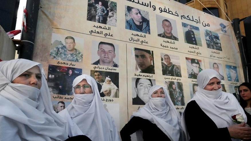 Lebanese Druze women stand next to posters with pictures of soldiers and policemen who were kidnapped by militants from the Islamic State group and al-Qaida's branch in Syria, the Nusra Front, in front of tents set up for a protest in downtown Beirut, Lebanon, Tuesday, Dec. 1, 2015. Syria's al-Qaida branch was releasing on Tuesday a group of Lebanese soldiers and policemen held captive since August 2014 as part of a swap deal brokered by Qatar that included Lebanon setting free an unspecified number of prisoners wanted by the militant group. (AP Photo/Bilal Hussein)
