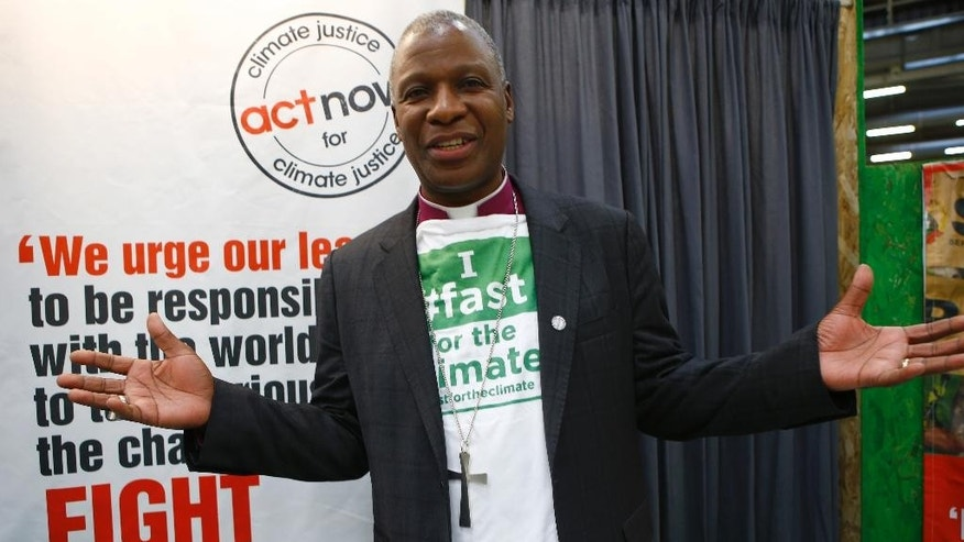 "Rev. Dr Thabo Makgoba, Archibishop of Cape Town, poses with a shirt reading ""I fast for the Climate"" the COP21, United Nations Climate Change Conference, in Le Bourget, outside Paris, Tuesday, Dec. 1, 2015. More than 10,000 interfaith clergy worldwide fast the first day of each month to call attention to the problem of global warming (AP Photo/Francois Mori)"