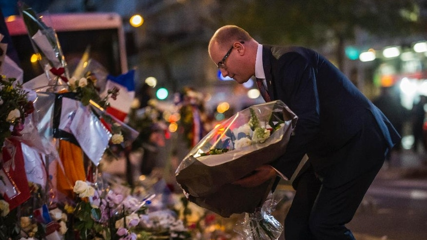 Czech Republic Prime Minister Bohuslav Sobotka pays his respects to victims of the Paris attacks in front of the Bataclan concert hall, in Paris, Monday, Nov. 30, 2015. The country remains on high alert for possible terrorist attacks after Islamic extremists killed at least 130 people in a rock concert massacre, shootings at Paris cafes and suicide bombings at the national stadium on Nov. 13. (AP Photo/Kamil Zihnioglu)