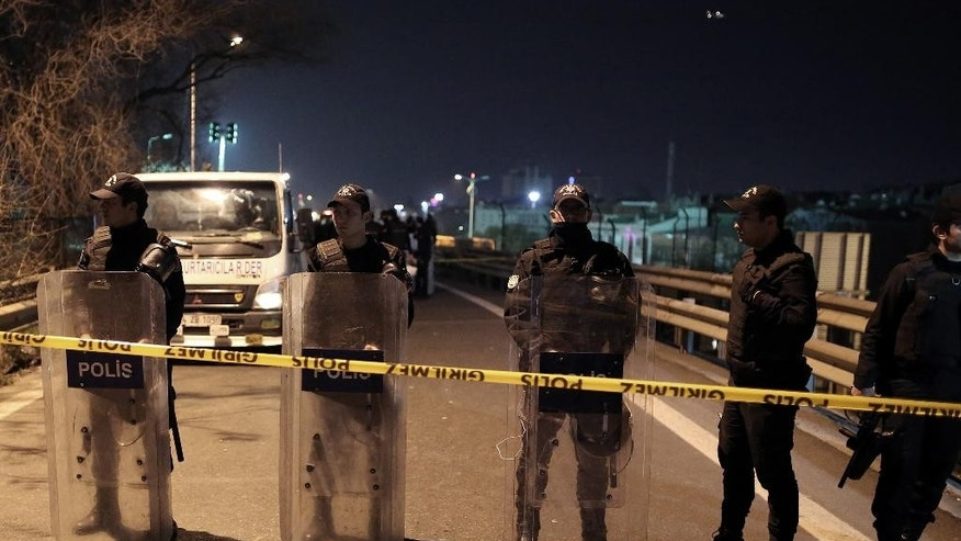 Riot police secure the area after an explosion on a highway overpass near a subway station, wounding five people, in Istanbul, Turkey, Tuesday, Dec. 1, 2015. The explosion was caused by a bomb left on barriers on the overpass, according to Atilla Aydiner, the mayor for Istanbul's Bayrampasa district.(AP Photo/Cagdas Erdogan)