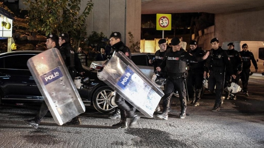 Riot police arrive after an explosion on a highway overpass near a subway station,  wounded five people and was caused by a bomb according to information given by the local mayor, in Istanbul, Turkey, Tuesday, Dec. 1, 2015. The bomb was left on barriers on the overpass, said Atilla Aydiner, the mayor for Istanbul's Bayrampasa district.(AP Photo/Cagdas Erdogan)