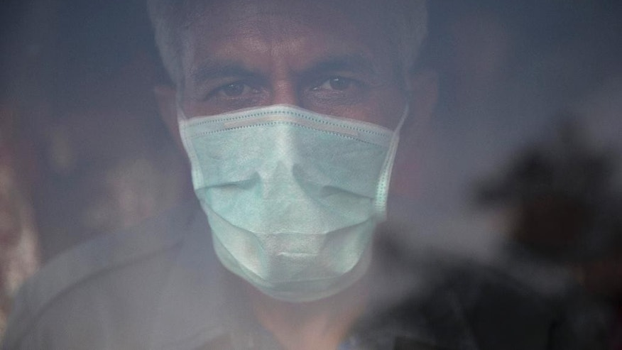 In this Nov. 25, 2015 photo, Sitesh Singh, 48, an auto rickshaw driver wears a mask to protect himself from pollution in New Delhi, India. Over the last decade the city's air pollution has grown so rapidly that the cold weather turns the city into a grey, smog-filled health nightmare. New Delhi has earned the dubious distinction of being the world's dirtiest city, surpassing Beijing, once the poster child for air pollution. (AP Photo /Tsering Topgyal)