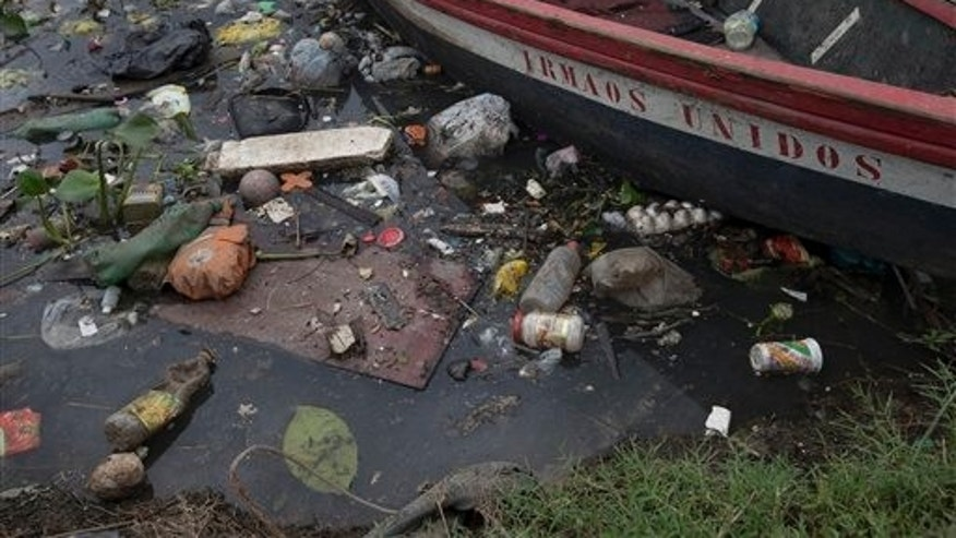 Trash surrounds a boat docked on the banks of the Meriti River, which flows into Guanabara Bay in Rio de Janeiro, Brazil, in November 2015. (AP Photo/Silvia Izquierdo)