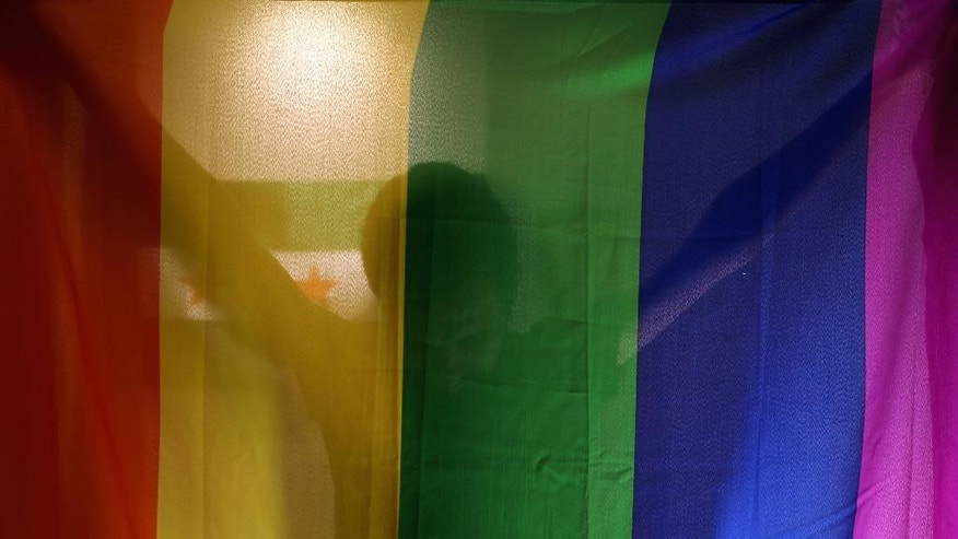 In this Oct. 22, 2015, photo, Daniel Halaby, a gay Syrian who fled from the Islamic State group, poses with the rainbow flag symbolic of LGBT rights in his apartment in southern Turkey. Halaby and others say the militants often torture suspected homosexuals or pore through their laptops and mobile phones trying to track down other gay men. Gays often fear they could be turned over to the militants by friends or family because of the stigma against homosexuality. Halaby spoke on the condition that he be identified by the name he uses in his political activism, and that neither his face nor location be revealed. (AP Photo/Hussein Malla)