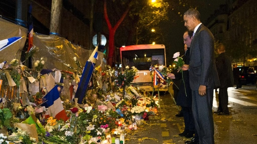 President Barack Obama, right, and French President Francois Hollande place flowers at the Bataclan, site of one of the Paris terrorists attacks, to pay his respects after arriving in town for the COP21 climate change conference Monday, Nov. 30, 2015, in Paris. (AP Photo/Evan Vucci)