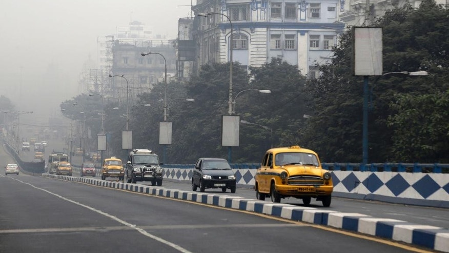 Cars move on a road engulfed in smog in Kolkata, India, Wednesday, Dec. 2, 2015. Last year, the World Health Organization ranked India's air pollution among the worst in the world. (AP Photo/ Bikas Das)