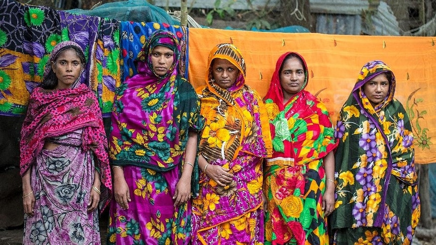 In this Nov. 18, 2015 photo, women who lost their homes to the River Meghna stand for a photograph at a government shelter in the island district of Bhola, where the Meghna River spills into the Bay of Bengal, Bangladesh. Though Prime Minister Sheikh Hasina has been internationally recognized for raising awareness of climate-change issues, Bangladesh has no specific plan for dealing with its own people displaced by climate-related disasters, other than offering them temporary shelter. (AP Photo/Shahria Sharmin)