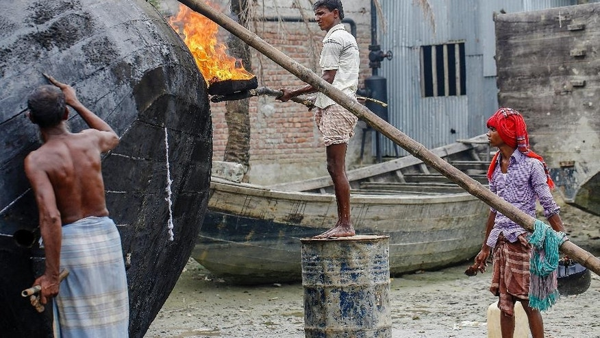 In this Nov. 17, 2015 photo, 18-year-old Mohmood Monir, right, who lost his home twice to river erosion repairs boats for a living, accompanied by his father and brother in the island district of Bhola, where the Meghna River spills into the Bay of Bengal, Bangladesh. (AP Photo/Shahria Sharmin)