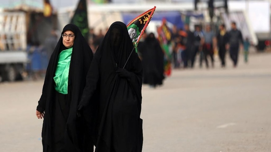 Shiite pilgrims march to Karbala for the Arbaeen ritual in Baghdad, Iraq, Tuesday, Dec. 1, 2015. The holiday marks the end of the forty day mourning period after the anniversary of the 7th century martyrdom of Imam Hussein, the Prophet Muhammad's grandson. (AP Photo/Hadi Mizban)