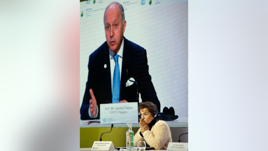 United Nations climate chief Christiana Figueres attends a news conference as French Foreign Minister Laurent Fabius is seen on the screen, at the COP21, the United Nations Climate Change Conference Wednesday, Dec. 2, 2015 in Le Bourget, north of Paris. Figueres and Fabius said Wednesday the climate talks are off to a good start thanks to 150 world leaders who came to Paris earlier this week, but now negotiations have to speed up and will get more complicated. (AP Photo/Christophe Ena)